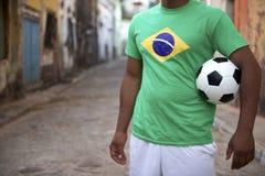 Brasilianischer Straßen-Fußball-Spieler, der Fußball hält stockbilder