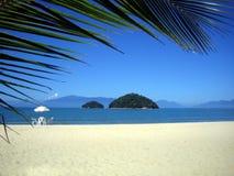 Brasilianischer Strand mit einem Stuhl und einer Insel Stockfotos