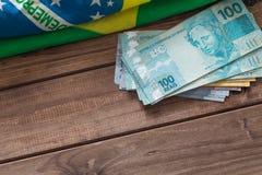 Brasilianisches Geld/Reais und Flagge auf dem Holztisch Stockfotografie