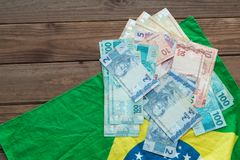 Brasilianisches Geld/Reais und Flagge auf dem Holztisch Stockbild