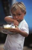 Brasilianisches Kind, das von der Kasserolle isst lizenzfreie stockfotos