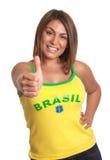 Brasilianisches Mädchen, das sich Daumen zeigt Lizenzfreies Stockfoto