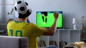 Brasiliansk fan som hurrar aktivt den hållande ögonen på matchen för favorit- fotbollslag på tv arkivfoton