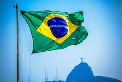 Brasiliansk flagga på bakgrunden av Kristus Förlossare arkivfoto