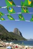 Brasiliansk flagga som Bunting den röda stranden Sugarloaf Rio Brazil Arkivfoto