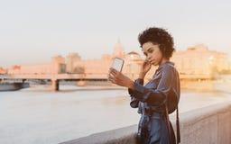 Brasiliansk flicka som fotograferar utomhus selfien nära en flod royaltyfri foto