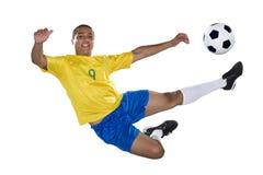 Brasiliansk fotbollspelare, banhoppning, guling och blått. royaltyfri fotografi