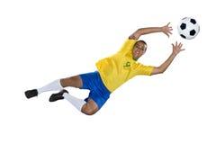 Brasiliansk fotbollspelare, banhoppning, guling och blått. arkivfoton