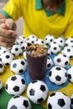 Brasiliansk fotbollspelare som äter Acai med fotbollar Fotografering för Bildbyråer
