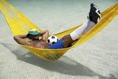 Brasiliansk fotbollspelare som kopplar av med fotboll i strandhängmatta royaltyfri bild
