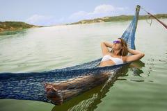 Brasiliansk kvinna på hängmattan i vatten royaltyfria bilder