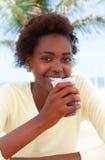 Brasiliansk kvinna på stranden som dricker sodavatten Arkivbild