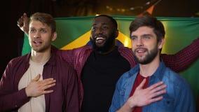 Brasilianska blandras- fotbollsfan som sjunger nationalsången, vinkande flagga i bar lager videofilmer