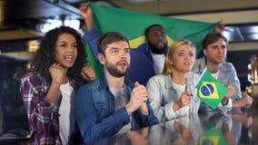 Brasilianska fotbollfans med flaggan som hurrar för landslaget som hoppas för seger royaltyfri bild