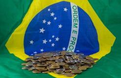 Brasilianska mynt, på bakgrundsflaggan av Brasilien Finansiell verklighet royaltyfri bild