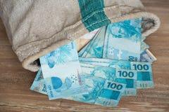 Brasilianska pengar, reais/på den bankpåsen/affärsidéen Arkivfoto