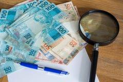 Brasilianska pengar, reais som, högt är nominella med ett ark av papper och en penna för beräkningar Arkivfoton