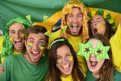 Brasilianska sportfotbollfans som firar seger tillsammans. Royaltyfria Bilder