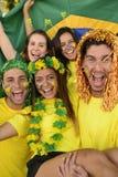 Brasilianska sportfotbollfans som firar seger tillsammans. Arkivbilder