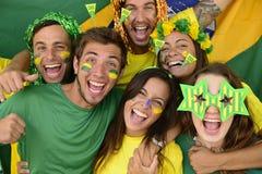 Brasilianska sportfotbollfans som firar seger tillsammans. Royaltyfri Foto