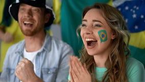 Brasilianska supportrar som firar seger av landslaget, hållande ögonen på match i bar royaltyfri bild