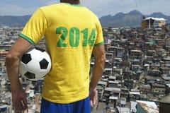 Brasilien fotbollsspelare 2014 med för Favela för fotbollboll Rio de Janeiro slumkvarter Arkivfoto