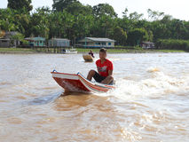 Brasilien: Pojke i ett motoriskt fartyg på en skattskyldig amason Royaltyfri Bild