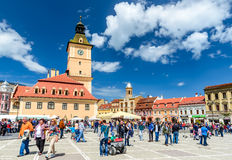 Brasov, Romania. 27 APRIL 2014: Scenery with tourists walking in Main Square, landmark with Council House in medieval center of Brasov, Transylvania, Romania Stock Image