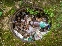 Sewage without a cover filled with  plastic beer bottle and trash . royalty free stock images