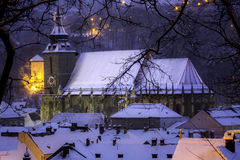 Brasov, Transylvania, Romania - December 28, 2014: A view of the medieval Black Church. At night after a snow fall and of one of the towers overlooking the city Royalty Free Stock Photos