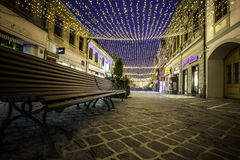 Brasov, Transylvania, Romania - December 28, 2014: A view of one of the main streets in downtown Brasov. Christmas lights over the main street in Brasov Stock Photos