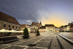 Brasov, Transylvania, Romania - July 28, 2015: Brasov Council Square is the historical center of the city. The sun was setting behind the medieval Black Church Stock Image