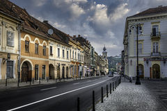 Brasov, Transylvania, Romania - July 28, 2015: A view of one of the main streets in downtown Brasov. Going down from the city square and passing by a Catholic Stock Photos
