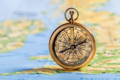 Brass antique compass on map background. Antique brass compass background object decorative equipment Royalty Free Stock Images