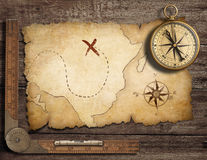 Brass antique nautical compass with old map. Aged brass antique nautical compass on table with old treasure map stock photo