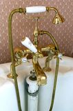 Brass bath taps. Edwardian brass bath fixture with mixer taps shower attachment and pull up waste plug royalty free stock photography