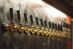 Brass beer Bar taps. Over a brushed stainless steel backdrop in a brewery stock photo