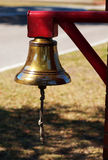 Brass bell hanging from red post. A brass bell on a red post with rope hanging down royalty free stock photos