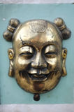 Brass / bronze chinese mask on green cement wall Stock Photography