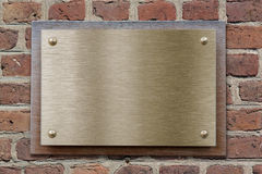 Brass or bronze metal plate on brickwall Stock Photo