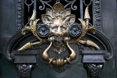 Brass brown knocker in a green  door Stock Images