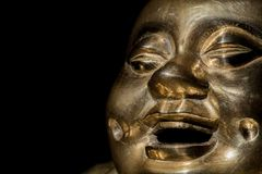 Brass buddha. Happy laughing monk face in close-up. Against black background with copy space. Cheerful Zen buddhism image of a traditional Budai statue royalty free stock photography