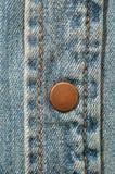 Brass button on denim. One brass button on a denim shirt Stock Image