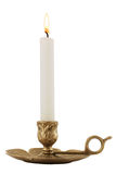 Brass Candleholder. Decorative antique brass candelabra with brightly lit white pillar candle. Isolated over white royalty free stock image