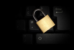 Brass closed padlock on a black keyboard Stock Photography