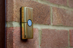 Brass-coloured doorbell on a brick wall Royalty Free Stock Photography