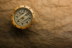 Brass Compass. Antique brass compass on weathered paper background Royalty Free Stock Photo