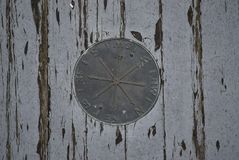 Brass compass medallion. This is a brass compass medallion inlay on the front porch of an aging boarded up house...prolly lead paint surrounding it royalty free stock photo