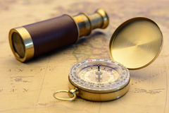 Brass compass and old telescope on vintage map world explorer concept. Old compass and old telescope on vintage map world explorer concept Royalty Free Stock Photography