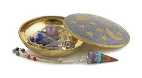 Selection of Radionics Dowsing Pendants. Brass dish on a white background containing three different dowsing pendulums and one Chakra coloured pendant laid in royalty free stock image